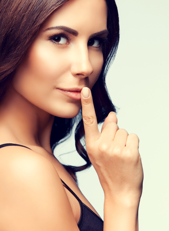 portrait of beautiful young brunette woman with finger on lips