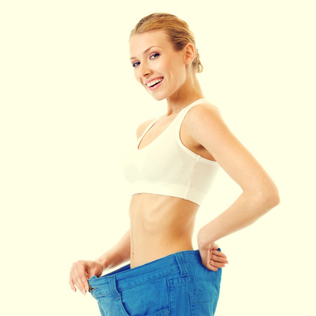 woman measuring waist: Young happy woman measuring waist with a tape measure in old jeans, health and dieting concept Stock Photo