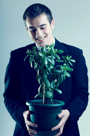 brunets: Young happy business man or student with flowerpot, focus on flowerpot.  Concept is: growing your own business