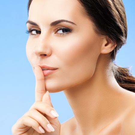 guardar silencio: Retrato de mujer joven manteniendo el dedo en sus labios y haciendo guardar silencio, sobre fondo azul