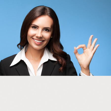 sales executive: Portrait of happy smiling young businesswoman in black suit, showing blank signboard with blank copyspace area for slogan or text, over blue background, showing okay gesture