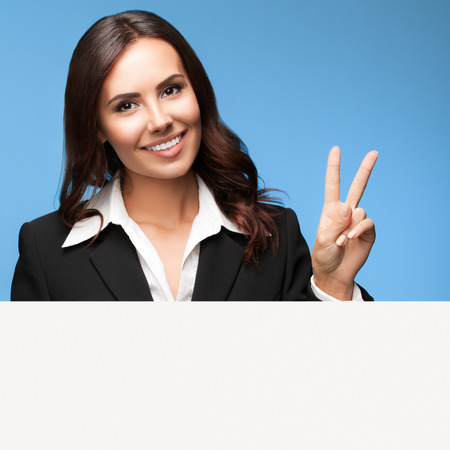 executive woman: Portrait of happy smiling young businesswoman in black suit, showing blank signboard with blank copyspace area for slogan or text, over blue background, showing two fingers or victiory gesture