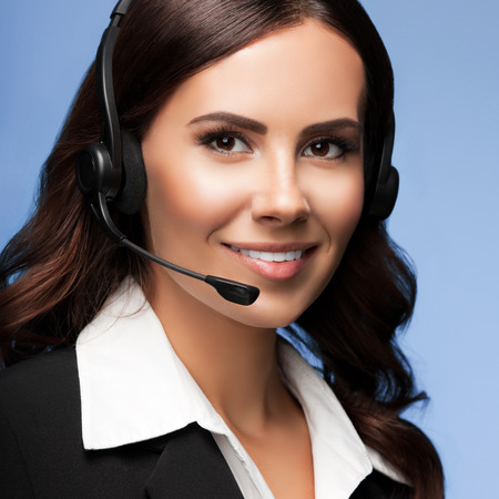 white suit: Portrait of cheerful customer support female phone operator in headset, over blue background. Consulting and assistance service call center.