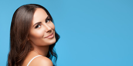 looking to camera: Portrait of happy smiling young beautiful woman in white casual clothing, over blue background, with copyspace area for slogan or text