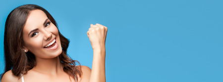 copies: Portrait of happy gesturing smiling young beautiful woman, in white casual clothing, over blue background, with copyspace area for slogan or text Stock Photo