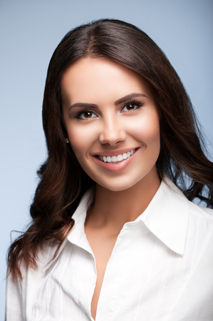business attire teacher: Portrait of happy smiling young cheerful brunette businesswoman, over grey background