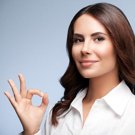 allright: Portrait of happy smiling young cheerful businesswoman, showing okay hand sign gesture, over grey background