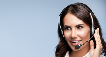 operator: Portrait of cheerful customer support female phone operator in headset, over grey background, with copyspace area for slogan or text message
