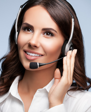 telephone call: Portrait of cheerful support female phone operator in headset, against grey background. Consulting and assistance service call center. Stock Photo
