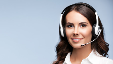 Operador de telefonía de atención al cliente femenino en auriculares, sobre fondo gris, con área de copyspace para lema o mensaje de texto Foto de archivo