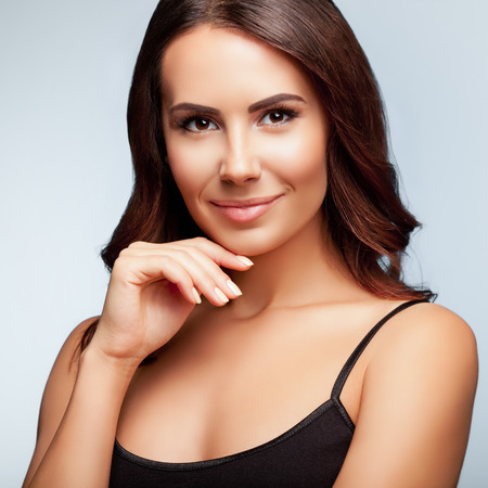 top clothing: portrait of thinking young woman in black tank top clothing, on bright grey background, square composition Stock Photo