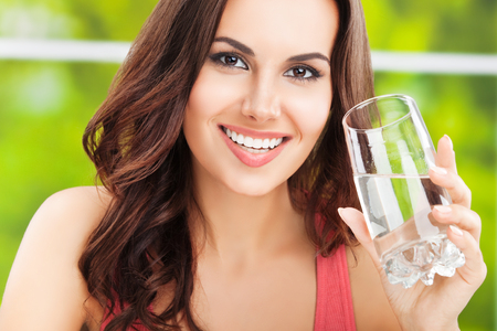 drink water: Portrait of young happy woman with glass of water Stock Photo