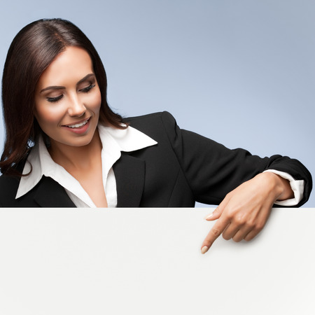 Portrait of happy smiling young businesswoman in black suit, showing blank signboard with blank copyspace area for slogan or text, over grey background