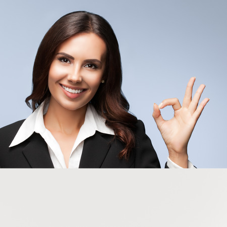 showing: Portrait of happy smiling young businesswoman in black suit, showing blank signboard with blank copyspace area for slogan or text, over grey background, showing okay gesture