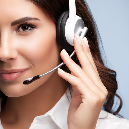hands free phones: customer support female phone worker, against grey background. Consulting and assistance service call center.