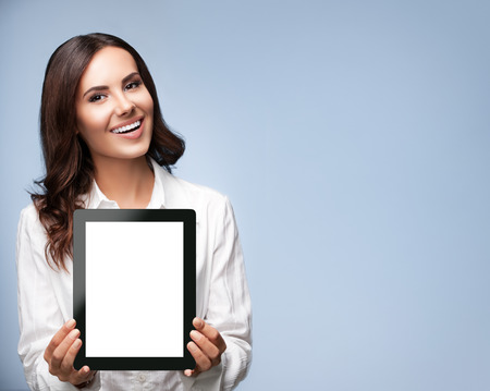 showing: Portrait of happy smiling brunette businesswoman showing blank no-name tablet pc monitor, over grey background, with copyspace area for slogan or text message
