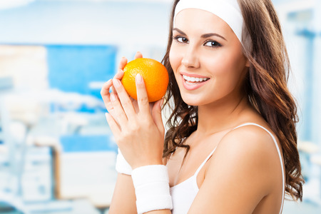 Portrait of happy smiling lovely woman with orange, at fitness center or gym Stock Photo