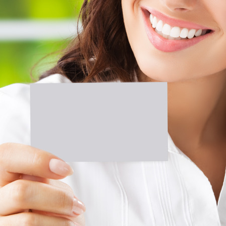 debet: Closeup of smiling businesswoman showing blank business or plastic card with copyspace area for slogan or text. Invitation concept.