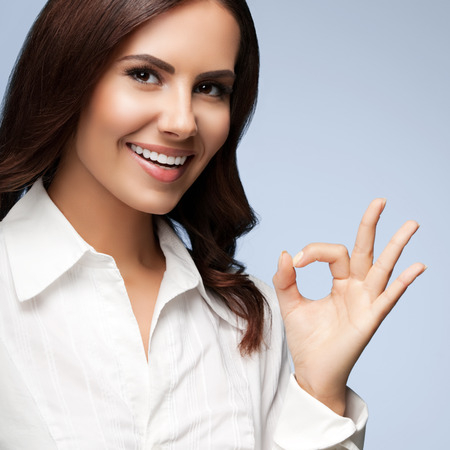 allright: Portrait of happy smiling young cheerful businesswoman, showing okay hand sign gesture, on grey
