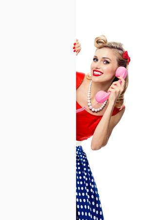 blank center: Portrait of smiling blond woman with phone, in pin-up style dress, showing blank signboard with copyspace area for slogan or text, isolated over white background. Caucasian blond model posing in retro fashion and vintage concept studio shoot.