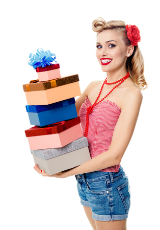 upsweep: Portrait of beautiful young happy smiling woman in pin-up style clothing, holding gift boxes, isolated over white background. Caucasian blond model posing in retro fashion and vintage concept studio shoot. Stock Photo