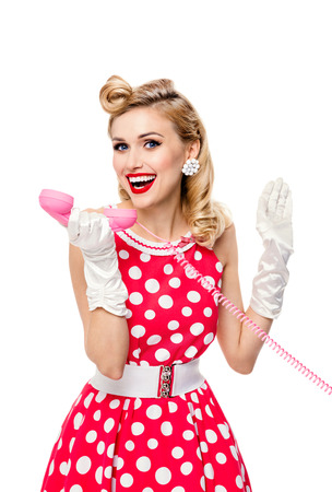 Funny portrait of beautiful young happy smiling woman with phone, dressed in pin-up style red dress in polka dot and white gloves, isolated over white background. Caucasian blond model posing in retro fashion and vintage concept studio shoot.