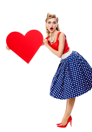 Full body portrait of beautiful young happy smiling woman holding heart symbol, dressed in pin-up style dress with polka dot, isolated over white background. Caucasian blond model posing in retro fashion and vintage concept studio shoot.