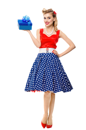 Full body portrait of beautiful young happy smiling woman dressed in pin-up style dress with polka dot, isolated over white background. Caucasian blond model posing in retro fashion and vintage concept studio shoot. Archivio Fotografico