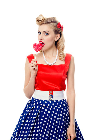 Portrait of beautiful young woman eating colourful lollipop, dressed in pin-up style dress in polka dot, isolated over white background. Caucasian blond model posing in retro fashion and vintage concept studio shoot. Stock Photo