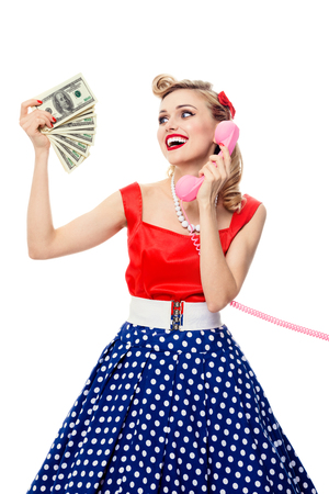 funny people: Portrait of beautiful young happy smiling woman with money, talking on phone, dressed in pin-up style dress in polka dot, isolated over white background. Caucasian blond model posing in retro fashion and vintage concept studio shoot.