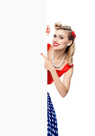 Portrait of happy smiling blond woman in pin-up style dress, showing blank signboard with copyspace area for slogan or text, isolated over white background. Caucasian blond model posing in retro fashion and vintage concept studio shoot.