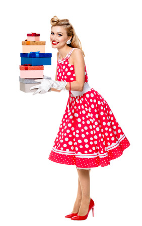 Full body portrait of beautiful young happy smiling woman in pin-up style red dress in polka dot and white gloves, holding gift boxes, isolated over white background. Caucasian blond model posing in retro fashion and vintage concept studio shoot.
