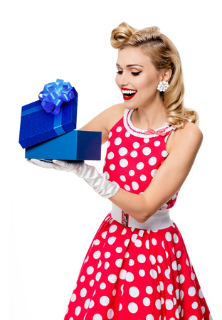 upsweep: Portrait of beautiful young happy smiling woman dressed in pin-up style red dress in polka dot and white gloves, isolated over white background. Caucasian blond model posing in retro fashion and vintage concept studio shoot.