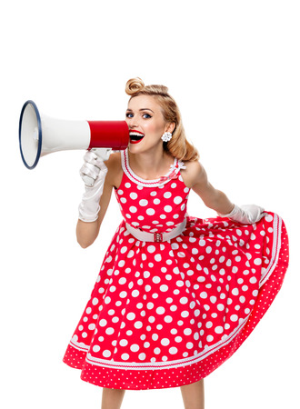 upsweep: Portrait of beautiful young happy woman holding megaphone, dressed in pin-up style red dress in polka dot and white gloves, isolated over white background. Caucasian blond model posing in retro fashion and vintage concept studio shoot. Stock Photo