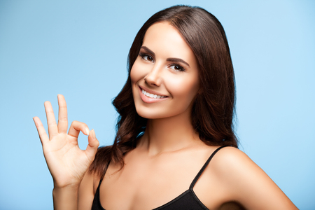woman smiling: portrait of beautiful young smiling brunette woman showing okay gesture, on bright blue background Stock Photo