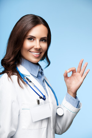 clinical: Portrait of happy smiling young female doctor showing okay hand sign, on bright blue background Stock Photo