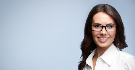 business attire teacher: Portrait of smiling young cheerful brunette businesswoman in glasses, over grey background, with copyspace area for slogan or text message