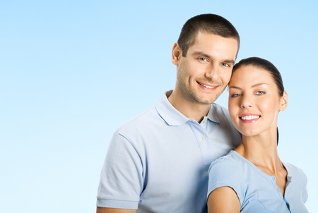 for text: Portrait of young smiling amorous attractive couple, over blue sky background, with blank copyspace area for text or slogan