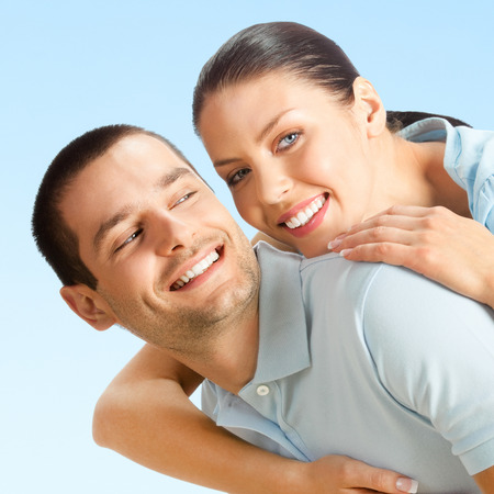 amorous: Cheerful young smiling amorous attractive couple, over blue sky background Stock Photo