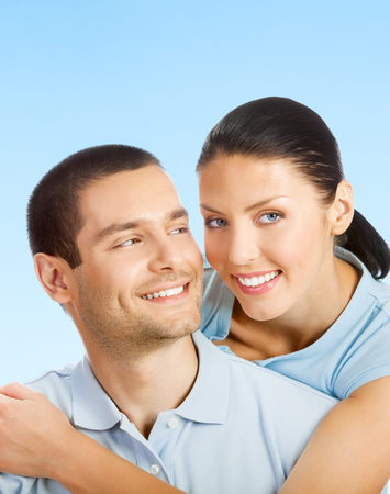 amorous: Portrait of young smiling amorous attractive couple, over blue sky background, with blank copyspace area for text or slogan