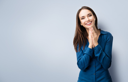 Portrait of happy gesturing smiling young woman in casual smart blue clothing, with copyspace for slogan or text message Standard-Bild