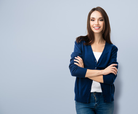 casual clothing: Portrait of young smiling woman in casual smart blue clothing with crossed arms, with copyspace for slogan or text message