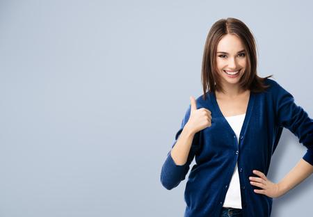 Porträt in casual smart blau Kleidung schöne junge Frau lächelnd, Daumen nach oben Geste, mit Exemplar für Slogan oder eine Textnachricht
