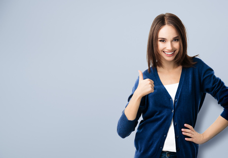 Portrait de sourire belle jeune femme dans les vêtements bleu chic et décontracté, montrant thumbs up geste, copyspace pour slogan ou message texte