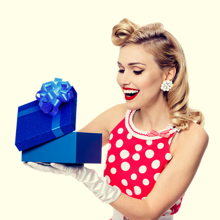 upsweep: Portrait of beautiful young happy smiling woman dressed in pin-up style red dress in polka dot and white gloves. Caucasian blond model posing in retro fashion and vintage concept studio shoot.
