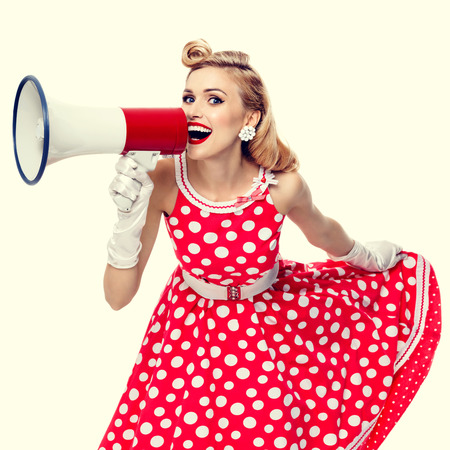 woman red dress: Portrait of beautiful young happy woman holding megaphone, dressed in pin-up style red dress in polka dot and white gloves. Caucasian blond model posing in retro fashion and vintage concept studio shoot. Stock Photo