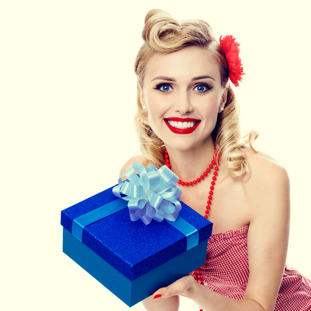 upsweep: Portrait of beautiful young happy smiling woman in pin-up style clothing. Caucasian blond model posing in retro fashion and vintage concept studio shoot. Stock Photo