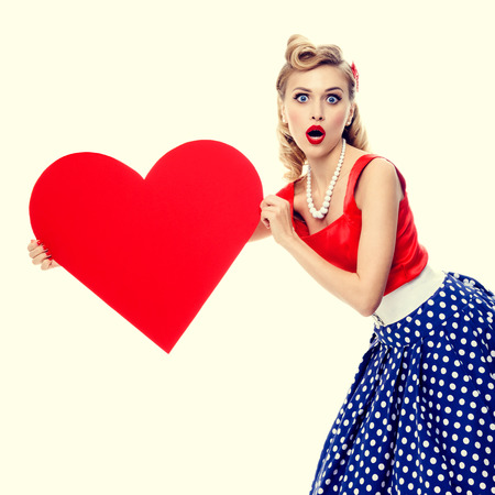 retro fashion: portrait of beautiful young happy smiling woman holding heart symbol, dressed in pin-up style dress with polka dot. Caucasian blond model posing in retro fashion and vintage concept studio shoot. Stock Photo