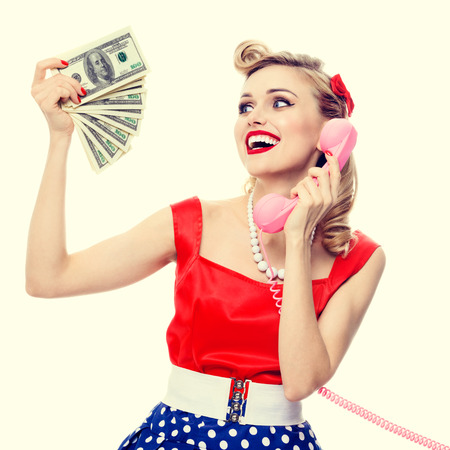 Portrait of beautiful young happy smiling woman with money, talking on phone, dressed in pin-up style dress in polka dot. Caucasian blond model posing in retro fashion and vintage concept studio shoot.
