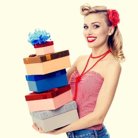 upsweep: Portrait of beautiful young happy smiling woman in pin-up style clothing, holding gift boxes. Caucasian blond model posing in retro fashion and vintage concept studio shoot.